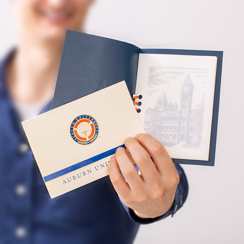 Hands holding a college announcement in blue and orange foil, along with a blue keepsake announcement holder.
