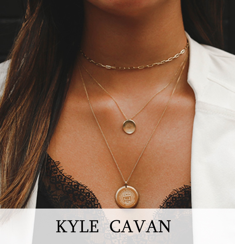 A woman in a white jacket, wearing a kyle cavan necklace.