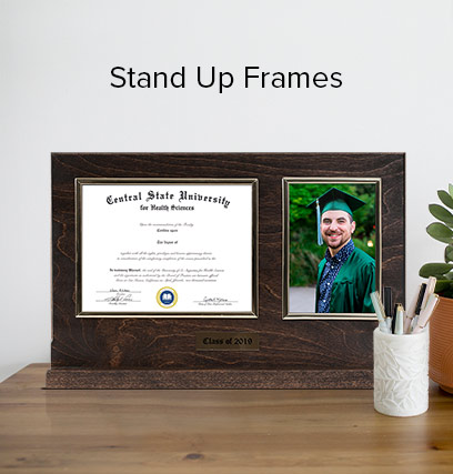A stand up frame sitting on a desk, next to a plant; and a pen holder, full of pens.