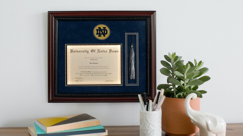 A diploma frame featuring a diploma, grad cap tassel and foil university logo, hanging above a desk.