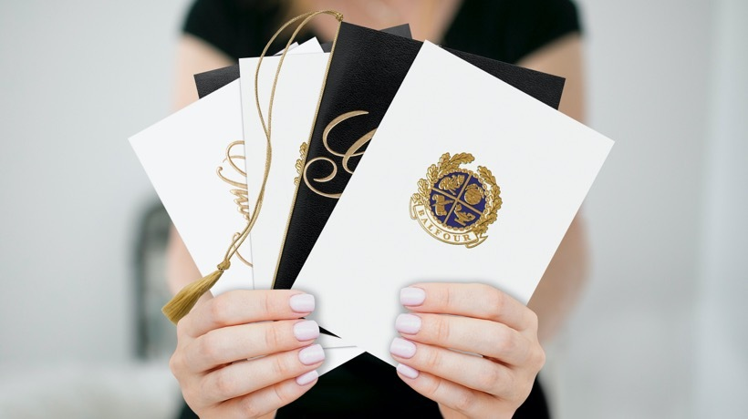 A woman's hands holding a coordinating gold-foil embossed announcement, thank you note, envelope and keepsake holder.