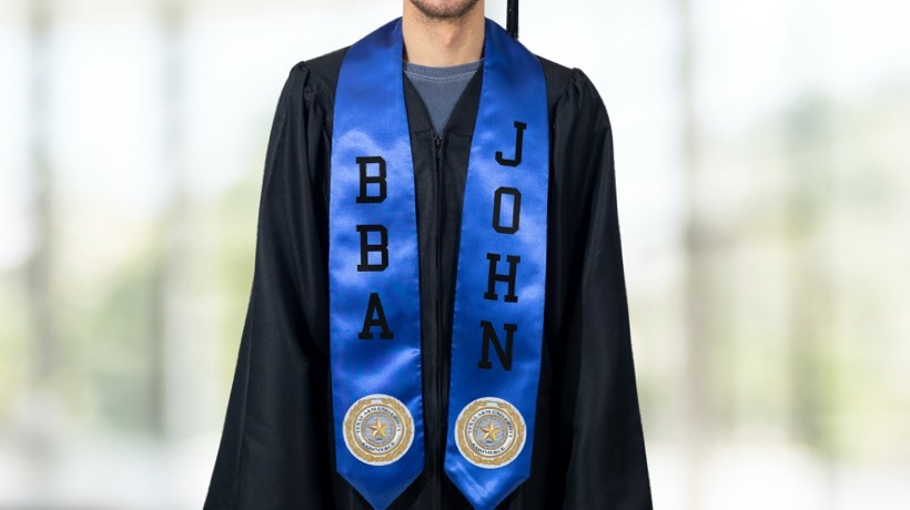 A grad in a black gown and blue personalized satin stole with custom letters and school patches.