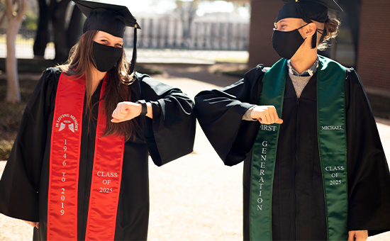 Two grads in cap, gown and mask bumping elbows. One with a red stole and one with a green stole.