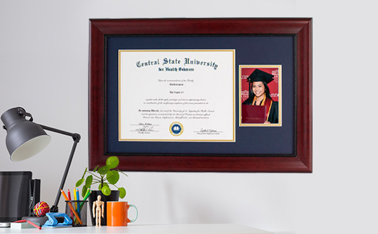 A diploma frame featuring a diploma and grad photo, hanging above a desk.
