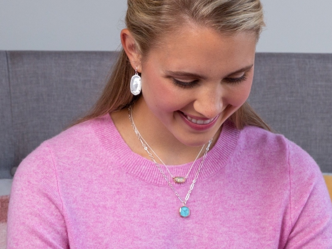 A woman wearing Kendra Scott Eaarrings, and Kendra Scott Necklaces ; from the Kendra Scott Mom and Teacher Collection
