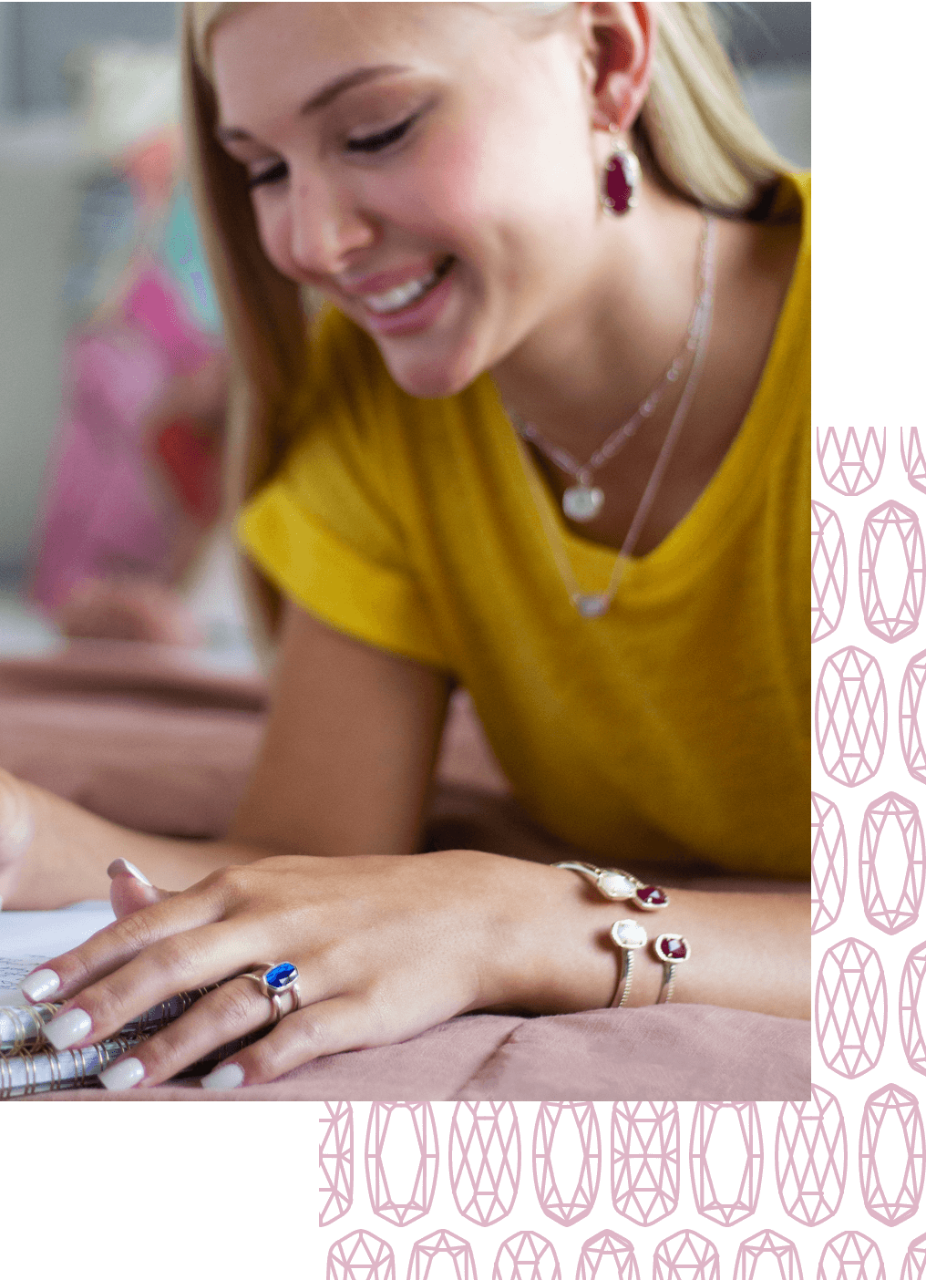 A women writing in a notebook, while wearing Kendra scott bracelets, necklaces; and a ring