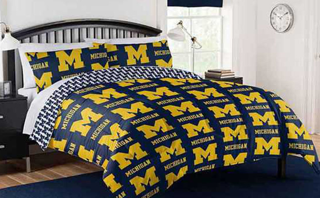 a bed with university of michigan pillows and comforter, next to a night stand