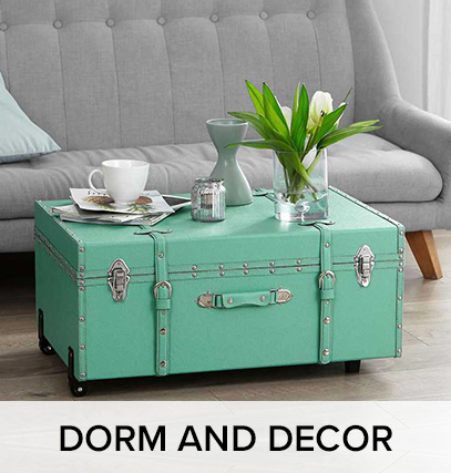"""a dorm trunk; with plants, a plate, and a coffecup sitting on it, next to a couch. Text that says """"dorm and decor"""""""
