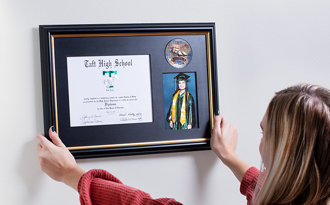 A woman hanging, a framed diploma on her wall