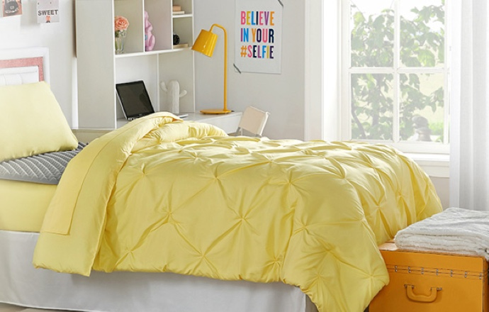 A yellow comforter set, on a bed; with a yellow trunk, at the foot of the bed