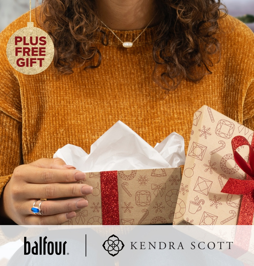 Woman opening gifts; wearing Kendra Scott jewelry.