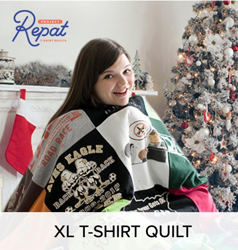 A woman in a customized t shirt quilt, next to a decorated tree and ; a fire place with stockings.