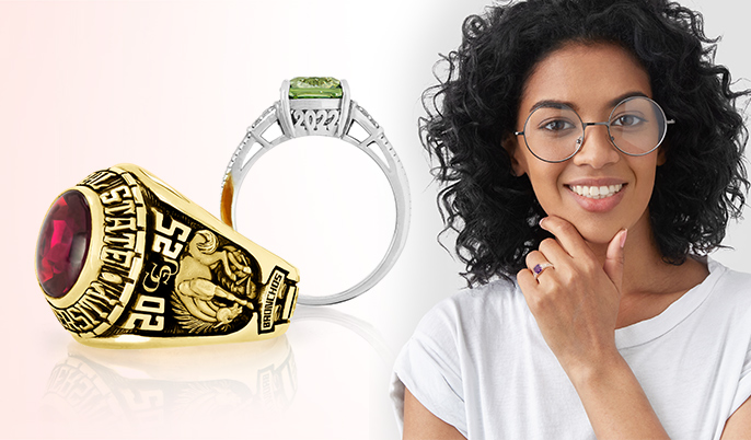 A woman, next to a gold men's high school ring, with red stone; and a silver women's college ring, with a green stone.