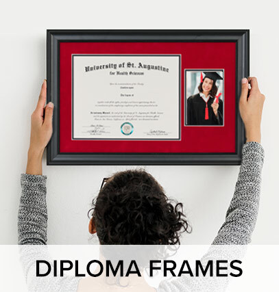 A woman hanging up a picture frame on the wall, with text under her saying'Diploma Frames'
