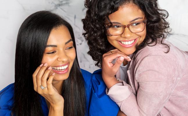 Two women wearing Kendra Scott jewelry.