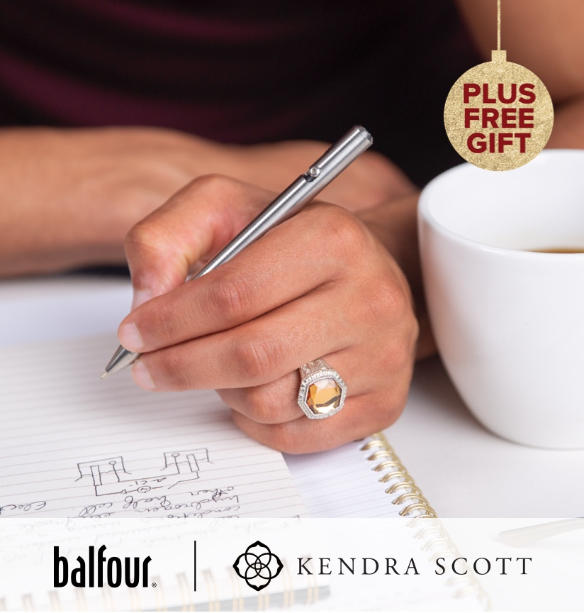A woman writing next, next to a cup of coffee; wearing a kendra scott ring
