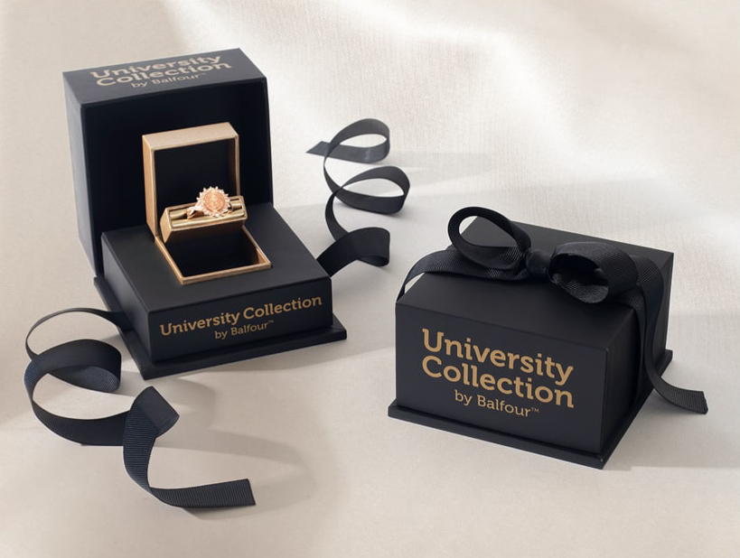 A open gift box, with a University Collection Ring in it; next to a closed University Collection gift box