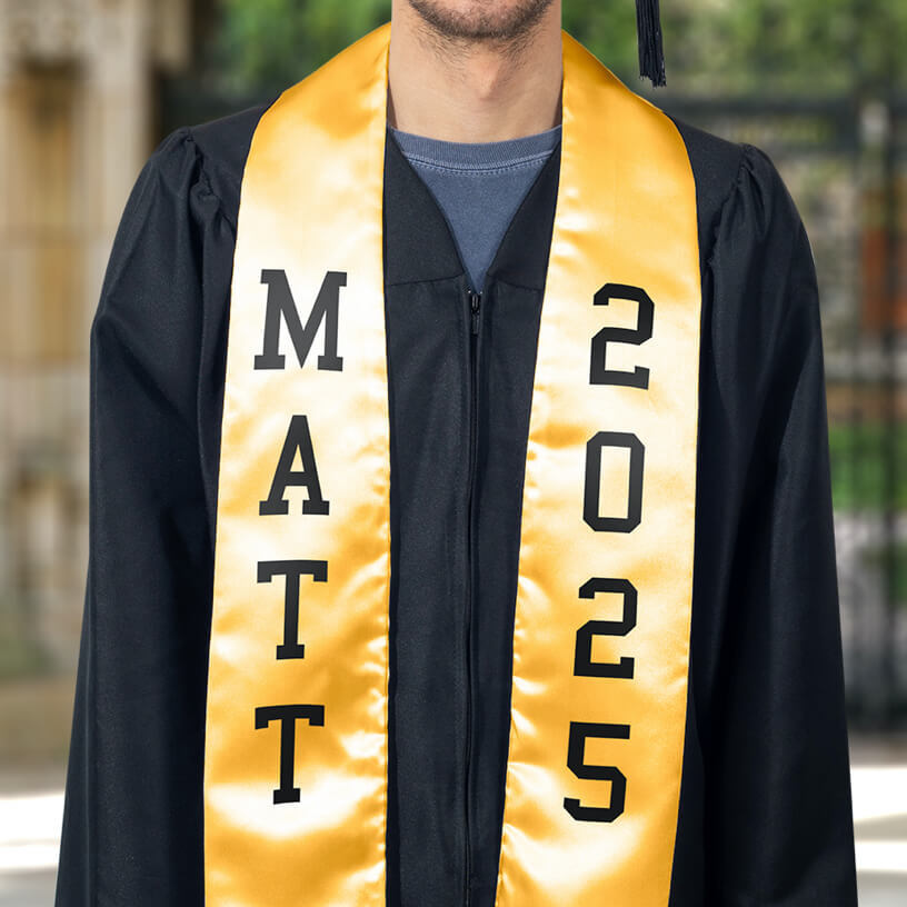 A graduate in a black graduation gown wearing a yellow stole with FlexStyle® text.
