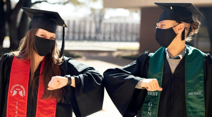 Two graduates wearing black caps, gowns, masks and stoles bumping elbows. Red stole on left grad, green stole on right grad.